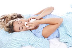 Junge Frau mit Taschentuch im Bett
